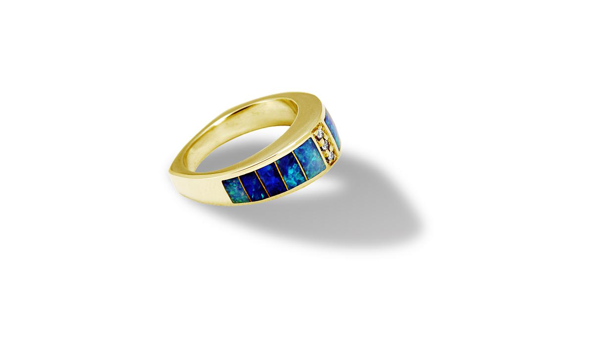 Gold ring with opal inlay on white background