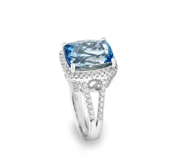 A large aquamarine stone on a ring surrounded by diamonds