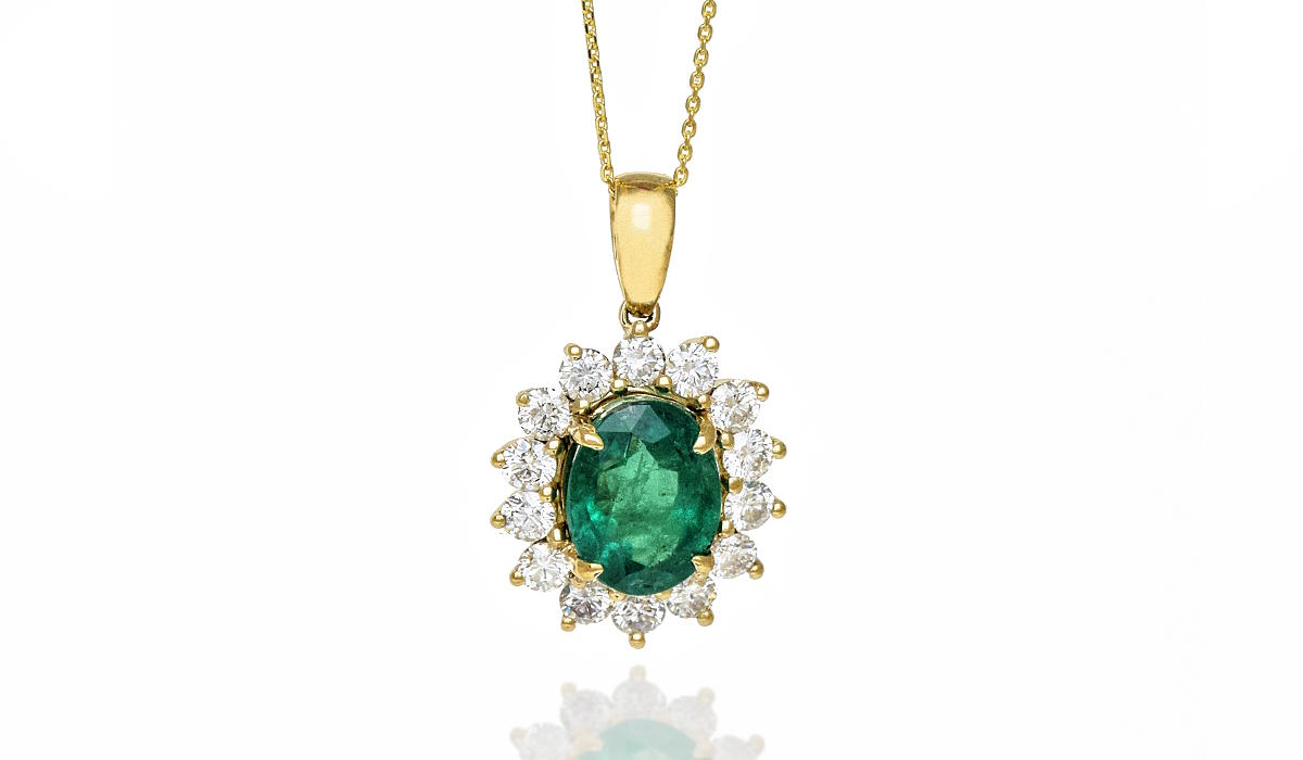 A gold pendant with an emerald surrounded by a cluster of diamonds