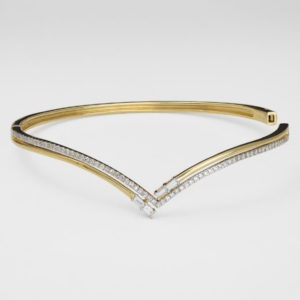 A thin gold bracelet with square and baguette diamonds